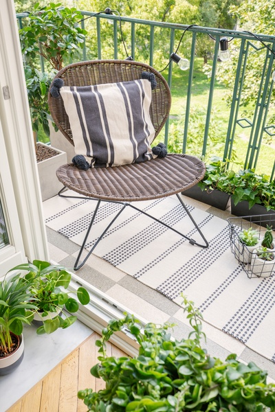 Relax zone on a balcony with a chair, rug and plants.