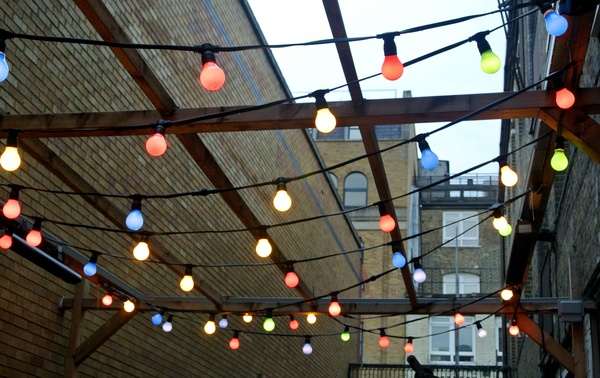 Decorative coloured lighting hanging from a wooden canopy