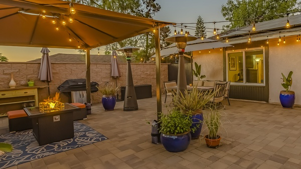 Cozy stone patio with string of lights over a covered seating and dining area