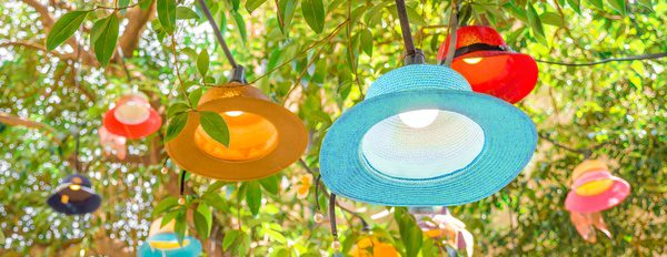 Original handmade multi-coloured lampshades hanging on tree