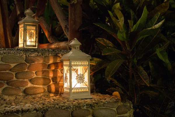 Two white lamps with burning flame on steps. Lantern in the evening garden.