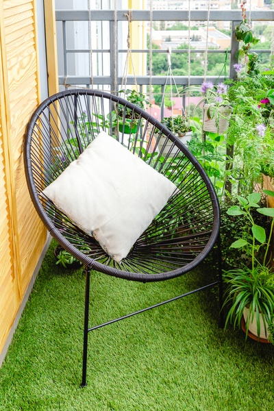 Garden chair with pillow on balcony at home in appartment on lawn grass with house plants flowers. Garden veranda modern terrace.