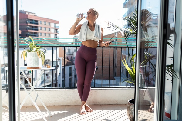 Sporty young woman drinking water while taking a break of doing exercise in balcony at home