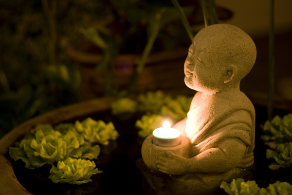Serene garden pond with Buddha statue and candle