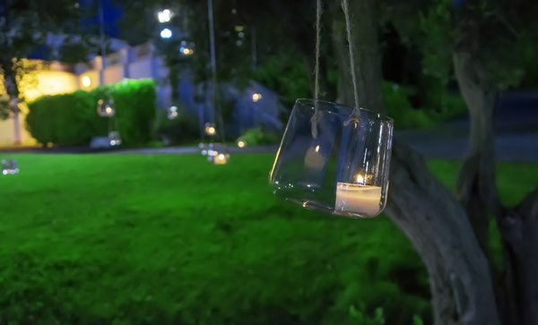 Candle in a glass hanging from a tree