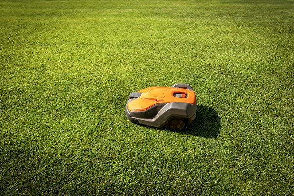 Automatic lawn mower robot moves on the green grass