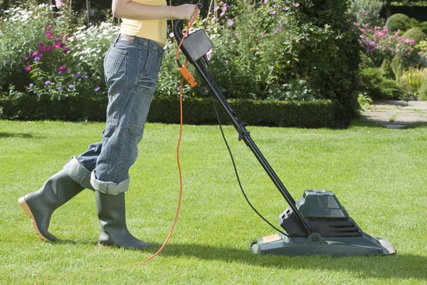 Woman Mowing Lawn with electric mower